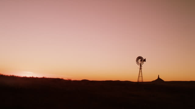 Timelapse of a windmill and Chimney Rock silhouetted against sunrise with clear skies