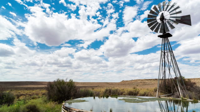 vidéos et rushes de timelapse of a windmill blowing in the wind next to and old zinc farm dam in a typical karoo landscape - karoo