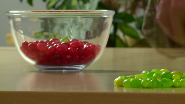 time-lapse of adding green jelly beans to bowl of red beans - ジェリービーンズ点の映像素材/bロール