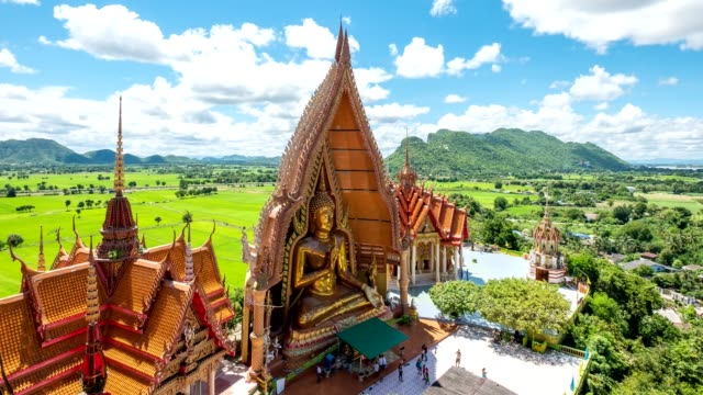 Time-lapse of Architecture golden big buddha with church and rice field at Wat Tham Sua, Tiger Cave, Kanchanaburi, Thailand