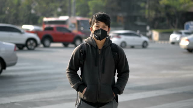 timelapse of asian man with mask standing in the traffic intersection air pollution with moving car in the background - pollution mask stock videos & royalty-free footage