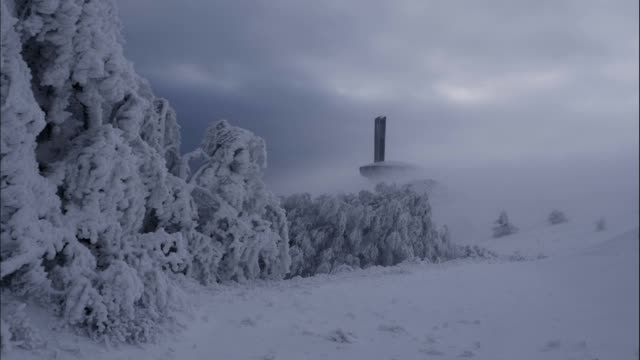 timelapse of beautiful, dramatic, fast moving clouds over a mountain peak in the winter, science fiction mood, buzludzha monument, ufo, frozen world - monumento video stock e b–roll