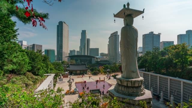 stockvideo's en b-roll-footage met timelapse van big buddha met rood esdoornblad bongeunsa tempel in het najaar in de gangnam district van seoul, zuid-korea. - korea