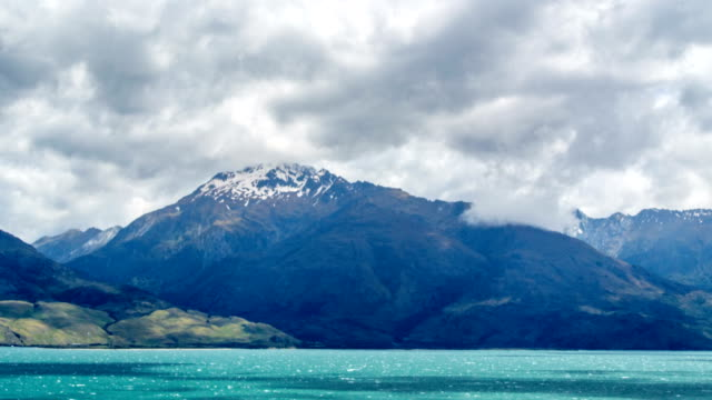 4k time-lapse of blue sky and clouds in lake wanaka, new zealand - water's edge stock videos & royalty-free footage
