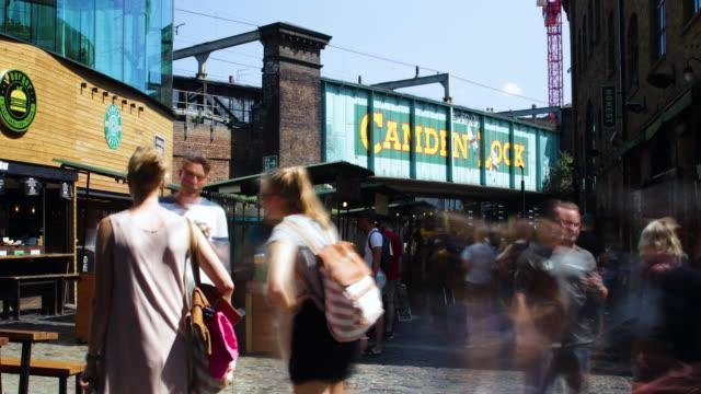 stockvideo's en b-roll-footage met time-lapse of busy camden market with views of camden lock railway bridge and market stalls - tijdopname