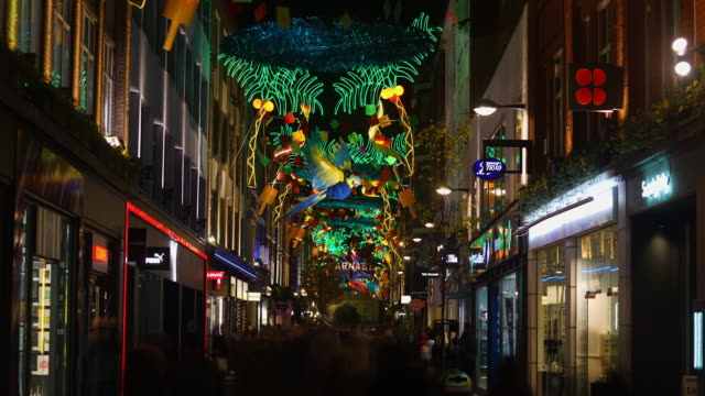 Time-lapse of busy Carnaby Street at night with colourful carnival Christmas decorations