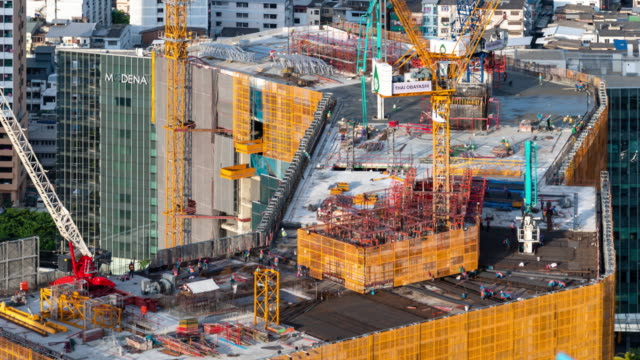 time-lapse of busy industrial construction site workers with cranes working - crane stock videos & royalty-free footage