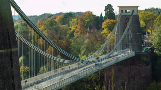 a timelapse of clifton suspension bridge during the day with autumn leaves on the trees surrounding - season stock videos & royalty-free footage