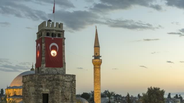 vídeos de stock, filmes e b-roll de timelapse da torre do relógio coberto com a bandeira da turquia e minarete - turquia