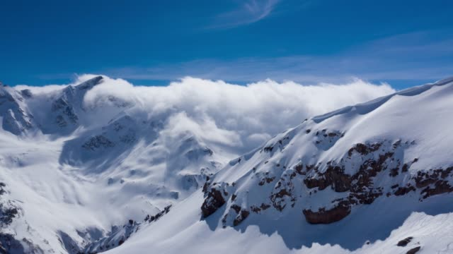 stockvideo's en b-roll-footage met timelapse of clouds and storm over high mountain landscape in the caucasus - sneeuwkap