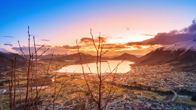 vidéos et rushes de timelapse de nuages étant éclairé par le soleil se coucher à minuit au cours d'une petite ville de l'eau. grand coup. - islande