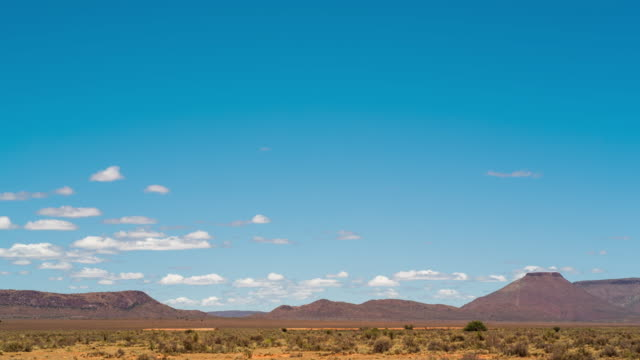 timelapse of clouds moving over an arid karoo landscape - karoo video stock e b–roll