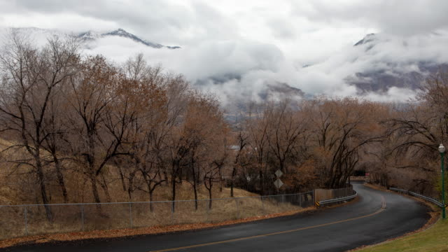 vídeos de stock e filmes b-roll de timelapse of clouds moving over mountains looking down road - provo