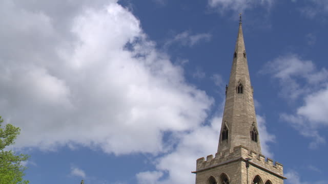 timelapse of clouds moving past church spire in bedford - spire stock videos & royalty-free footage
