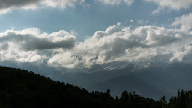 timelapse of clouds moving through high snowy peaks in kyrgyzstan - woodland stock videos & royalty-free footage
