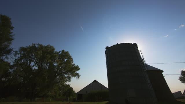 vidéos et rushes de timelapse of clouds over a farm silo barn - silo