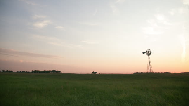 Timelapse of clouds over a windmill at sunset