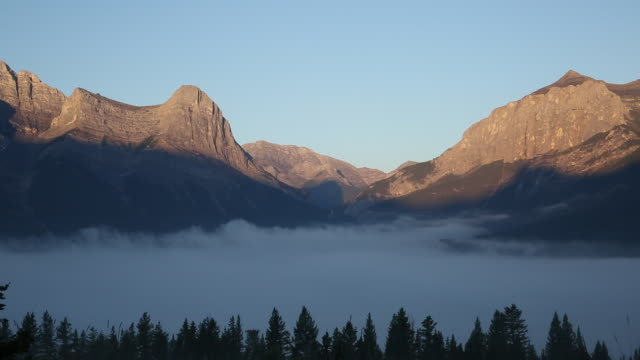 Time-Lapse of clouds passing through a mountain valley at sunrise
