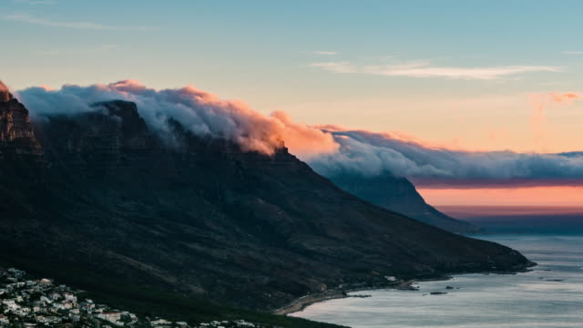 time-lapse of clouds pouring over table top mountains - cape town stock videos & royalty-free footage
