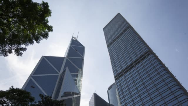 timelapse of clouds rolling through a blue sky above the cheung kong center right and the bank of china tower left in the central district of hong... - bank of china tower hong kong bildbanksvideor och videomaterial från bakom kulisserna