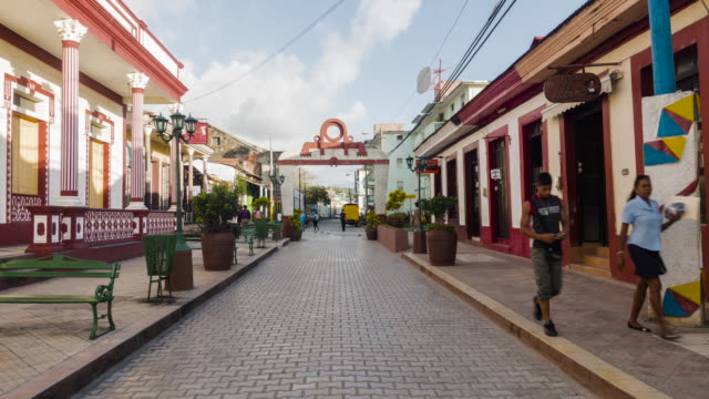 vídeos de stock, filmes e b-roll de timelapse of colonial baracoa cuba town. main pedestrian street. colonial city. people walking on a pedestrian road. establishing shot / b-roll - b roll
