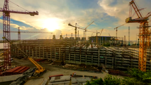 Time-lapse of Combine cycle power plant Construction Site with tower crane, Mobile crane and steel structure of boiler and cooling tower at dusk 60fps