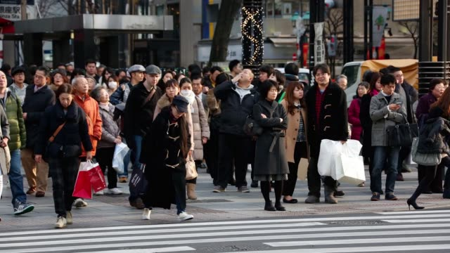 Timelapse of commuters crossing a road in the Ginza area of Tokyo Japan on Thursday Dec 24 2015