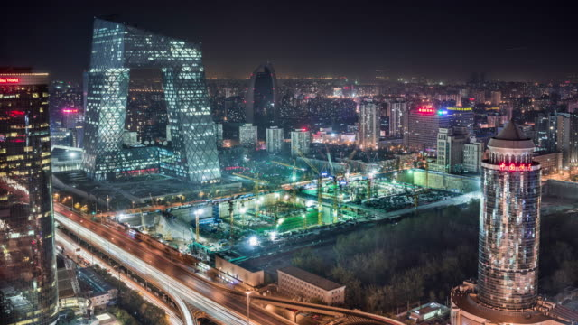 vídeos de stock e filmes b-roll de timelapse of construction site in front of ctv tower in beijing at night - pequim