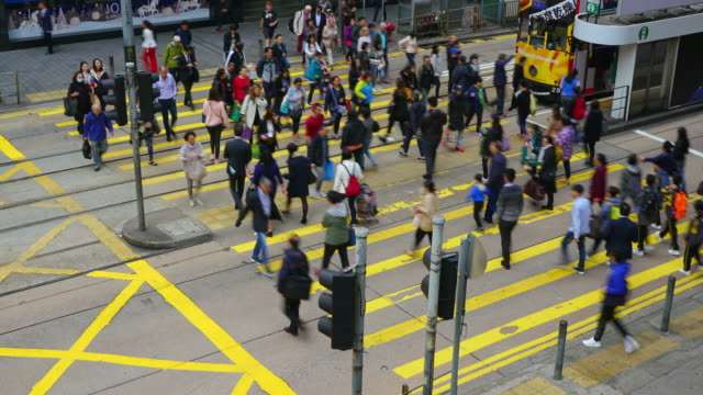 (zoom out) time-lapse of crowd crossing road at zebra crossing in hong kong. - central district hong kong stock videos & royalty-free footage