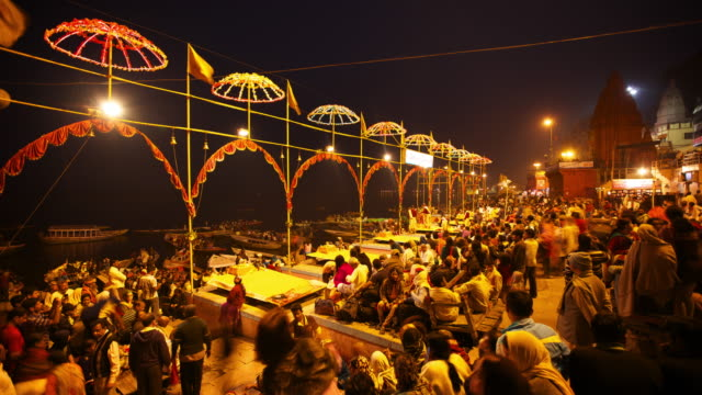 Timelapse of crowds of religious followers gathered on the busy riverbank to celebrate Kumbh Mela in India