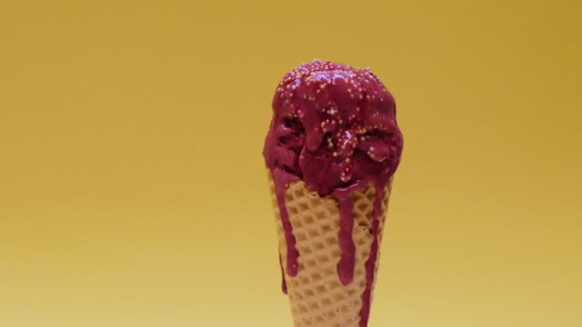 Time-lapse of dark pink ice cream with sprinkles melting against a yellow background