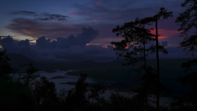 time-lapse of dusk over umiam lake with trees in foreground in shillon - ネイチャーズウィンドウ点の映像素材/bロール