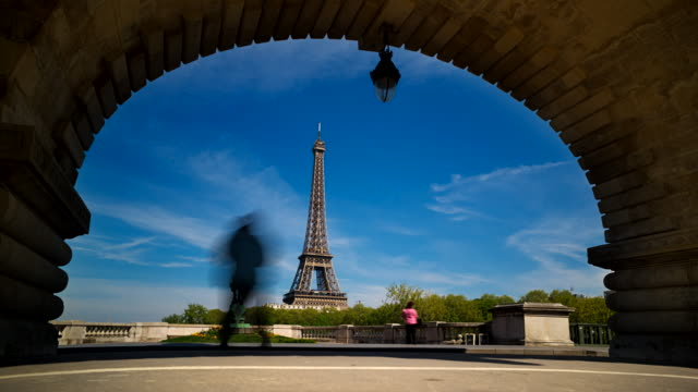 vídeos de stock e filmes b-roll de time-lapse of eiffel tower seen through an arch of the bir-hakeim bridge - arco caraterística arquitetural