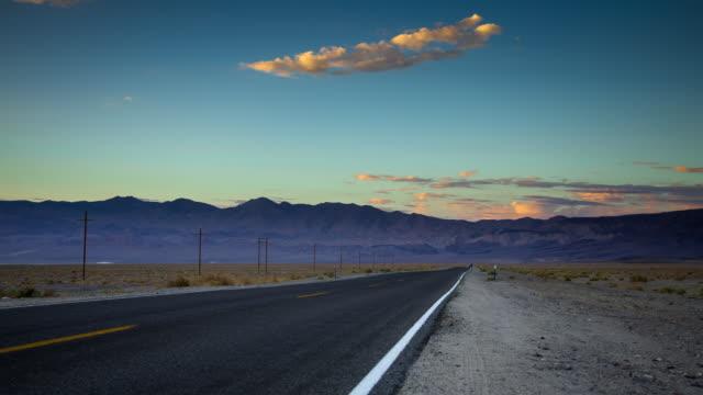 timelapse of empty desert highway at sunset - freie straße stock-videos und b-roll-filmmaterial