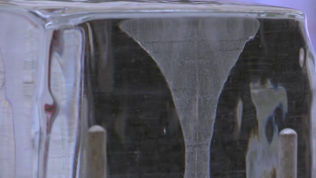 Time-lapse of experiment showing a weighted piece of wire cutting through a block of ice and the ice reforming