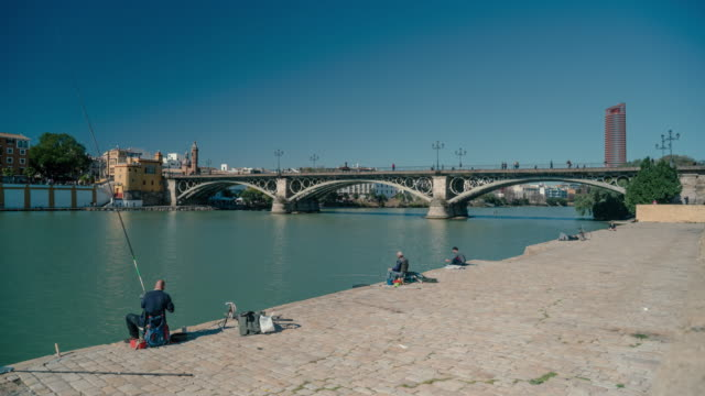 time-lapse of fishermen in front of the triana bridge, seville, spain - paving stone stock videos & royalty-free footage