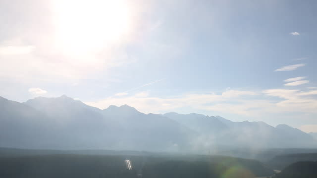 Time-Lapse of fog swirling around with the morning sun lighting distant mountains