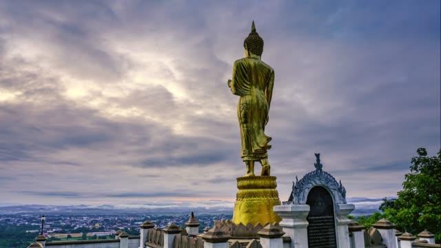 vídeos de stock, filmes e b-roll de tempo-lapso da estátua dourada de buddha com nebuloso opinião do céu e da cidade na manhã em wat phra isso kao noi, nan, norte de tailândia - norte