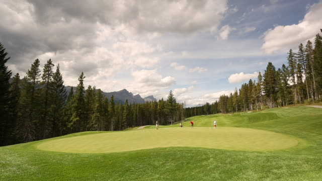 time-lapse of golfers on putting green with mountains in the background - abschlagen stock-videos und b-roll-filmmaterial