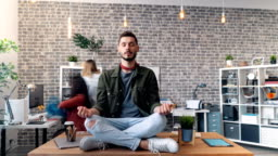 Time-lapse of handsome young man relaxing in lotus position on desk in office