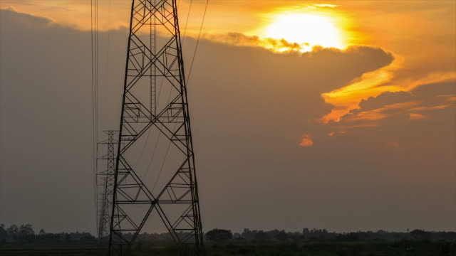 Timelapse of high electric pole in green paddy field at sunset