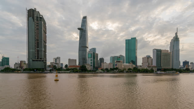 timelapse of ho chi minh city skyline and skyscraper in center of heart business at ho chi minh city downtown. panorama of cityscape on saigon river in ho chi minh city at vietnam from day to night - vietnam stock videos & royalty-free footage