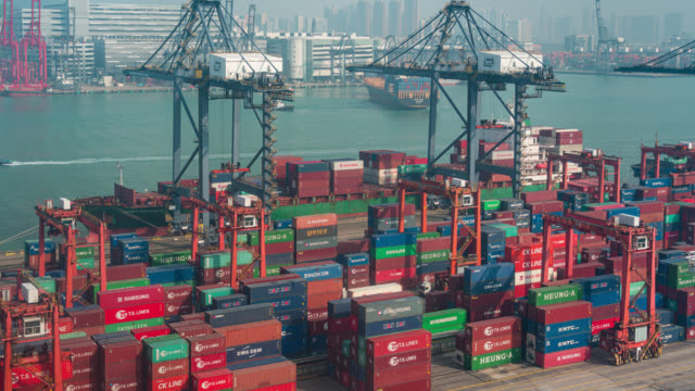 timelapse of international port with crane loading containers in import export business logistics at hong kong (zoom out) - ship stock videos & royalty-free footage