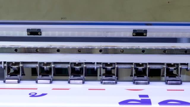 Time-lapse of Large format inkjet printer is printing Thai text on white vinyl