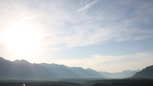 Time-Lapse of light clouds passing over misty alpine valley at sunrise