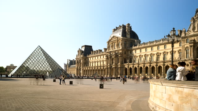 time-lapse of louvre museum on a sunny afternoon in paris, france - louvre stock videos and b-roll footage