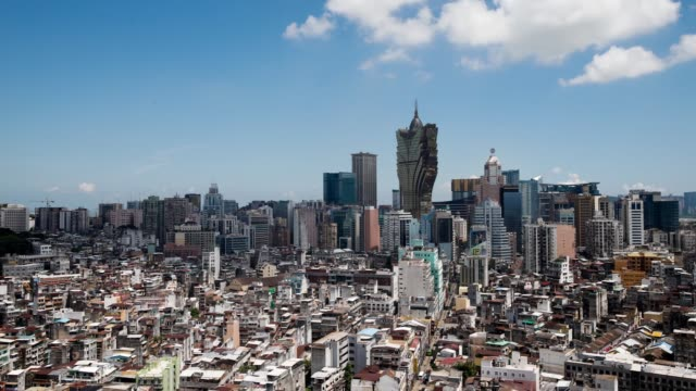 Timelapse of Macau Cityscape and skyline with Casino Grand Lisboa center operated by SJM Holdings Ltd center is seen through a window near commercial...