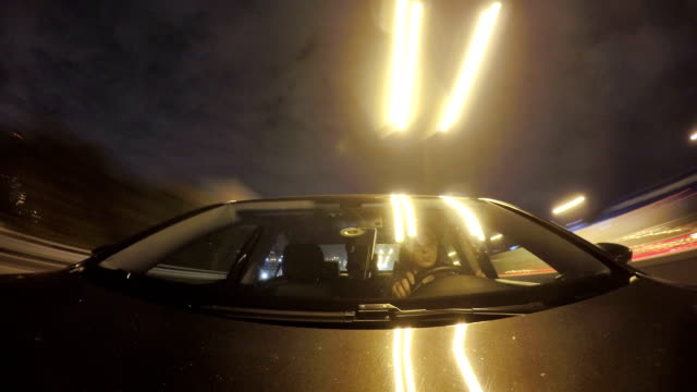 timelapse of man drives a car in the city at night. front view from the car body - フロントガラス点の映像素材/bロール