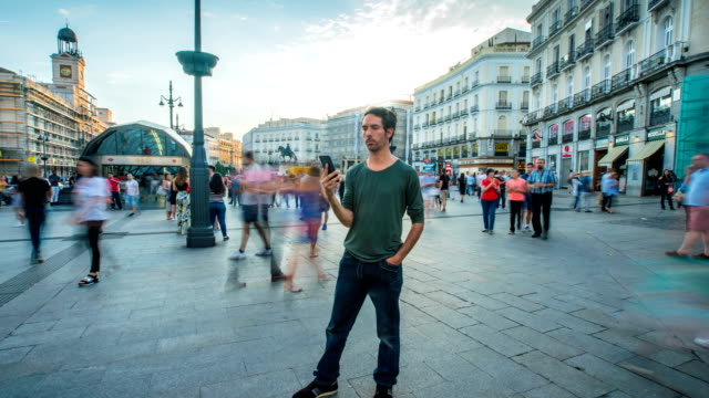 timelapse of man standing while the people move speedly - jeans stock videos & royalty-free footage