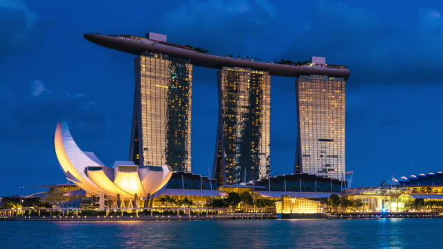 timelapse of marina bay sands at nightfall, singapore - marina bay sands stock videos and b-roll footage